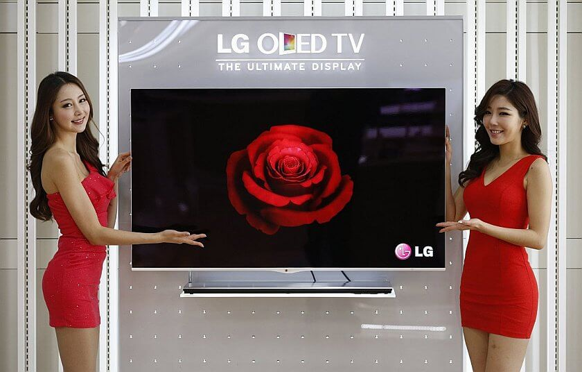 Models pose next to a LG Electronics' organic light-emitting diode (OLED) television in Seoul January 2, 2013. LG Electronics started taking orders on Wednesday for OLED televisions, hoping to take the initiative over its rival Samsung in the next-generation technology. OLED is more energy efficient and offers higher contrast images than LCD. It is so thin that future mobile devices will be unbreakable and will be able to be folded or rolled like paper. LG, the world's No.2 TV manufacturer, said it would start delivery of the new TVs from early February, with plans to display them at 1,400 retail outlets in South Korea. REUTERS/Lee Jae-Won (SOUTH KOREA - Tags: BUSINESS SCIENCE TECHNOLOGY)